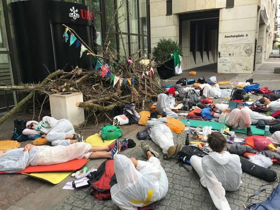In weissen Overalls gekleidet verbarrikadierten mehrere Dutzend Klimaaktivisten die Eingänge zu den UBS-Bürogebäuden bei der St. Alban-Anlage in Basel.