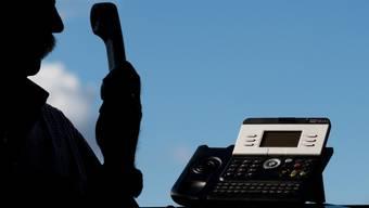 Ein Mann posiert zum Thema Enkeltrick-Betrug mit einem Telefon. (Symbolbild)