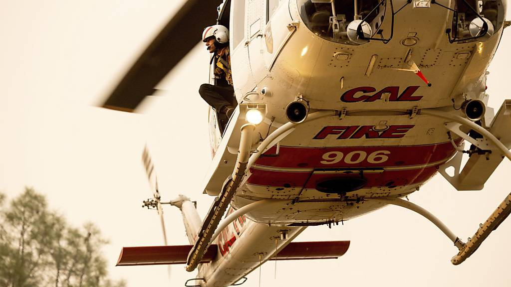 Ein Feuerwehrmann schaut aus einem Hubschrauber heraus, während er an den Löscharbeiten eines Waldbrandes beteiligt ist. Foto: Noah Berger/AP/dpa