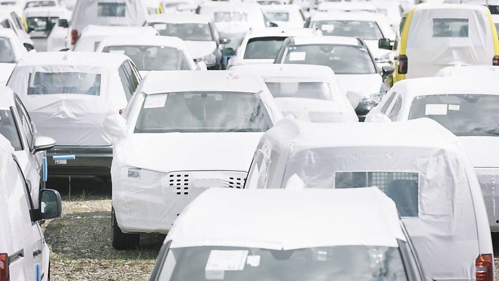 Neuwagen, die zum Schutz mit weisser Plane umhüllt sind, warten auf dem Parkplatz eines Autohändlers auf neue Besitzer. (Archivbild)