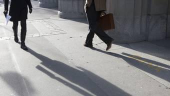 Passanten vor dem Hauptsitz UBS an der Zürcher Bahnhofstrasse: die Praxis mit Steuersündern wirft lange Schatten auf die Grossbank. (Archiv)