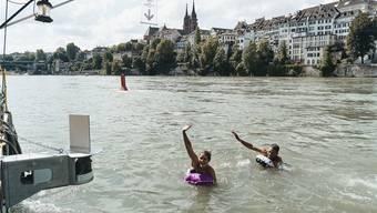 Links unten im Bild die Kamera, oben die Fahne und rechts die winkenden Rheinschwimmer. Bild: Roland Schmid (Basel, 29. Juli 2019)