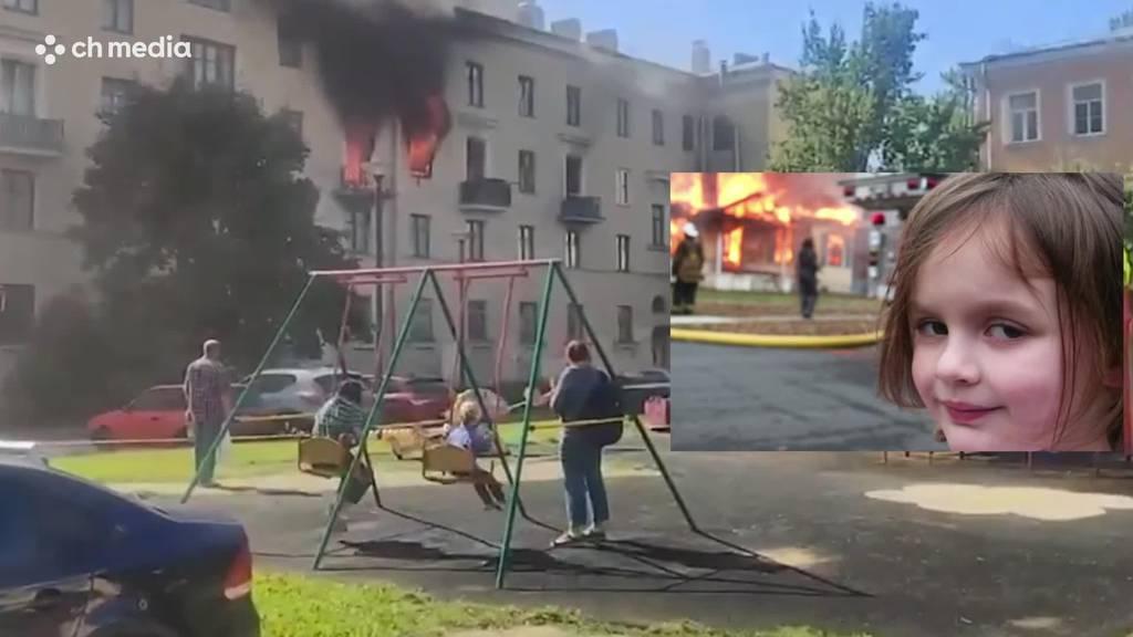 Kinder schaukeln - dahinter brennt das Haus