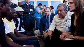 Angelina Jolie und Guterres (2. von rechts) sprechen auf lampedusa mit Flüchtlingen