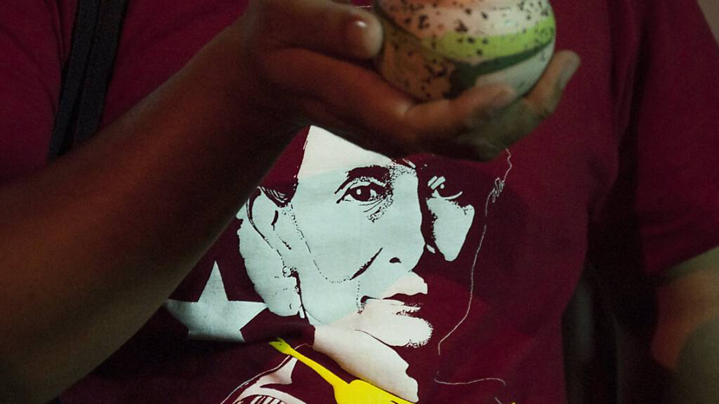 Ein Demonstrant hält während einer Demonstration eine brennende Kerze vor seinem T-Shirt mit einem Portrait von Aung San Suu Kyi, faktischer Regierungschefin von Myanmar, eine brennende Kerze. Foto: Peerapon Boonyakiat/SOPA Images via ZUMA Wire/dpa