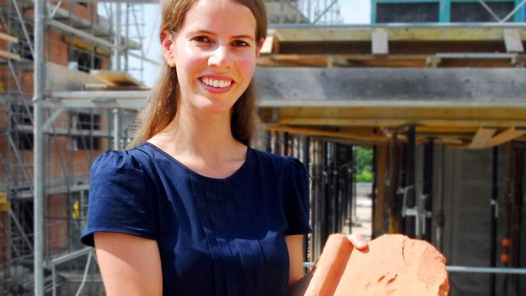 August 2012: Archäologin Mirjam Wullschleger mit einem ausgegrabenen Tonziegel, dahinter die Baustelle am einstigen Standort der Villa. fup