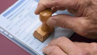 Das Dienstbüchlein eines Stellungspflichtigen wird gestempelt (Archiv)