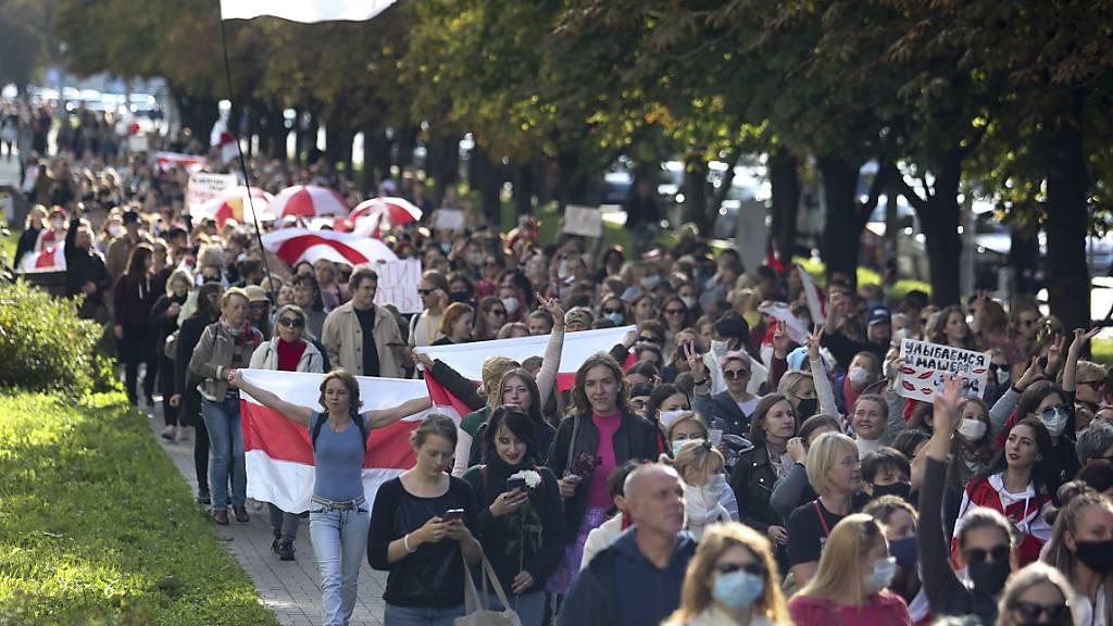 Frauen mit alten belarussischen Nationalflaggen gehen bei einer Demonstration gegen die Wahlergebnisse in Belarus über eine Straße. Foto: Uncredited/TUT.by/dpa