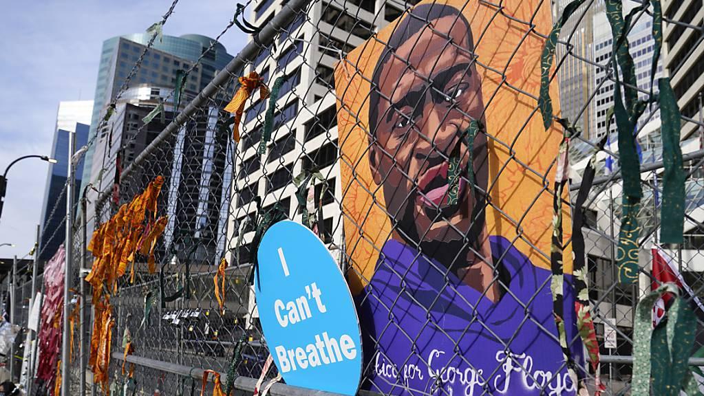 Ein Plakat mit einem Bild von George Floyd hängt an dem Zaun vor einem Regierungsgebäude von Hennepin County in Minneapolis. Foto: Jim Mone/AP/dpa