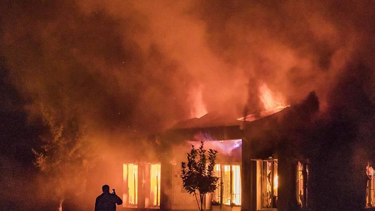 dpatopbilder - Ein Mann fotografiert mit einem Handy den Brand eines Gebäudes, nach dem Einschlag einer aserbaidschanischen Rakete. Foto: Celestino Arce Lavin/ZUMA Wire/dpa