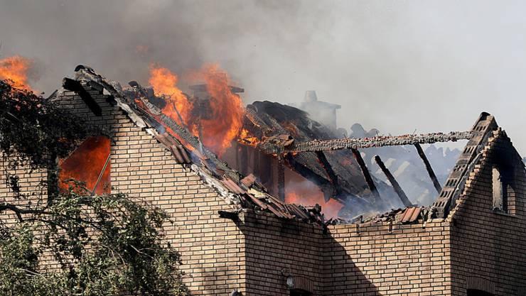 Flammen schlagen aus den Dachstühlen brennender Häuser an der Bahnstrecke in Siegburg.