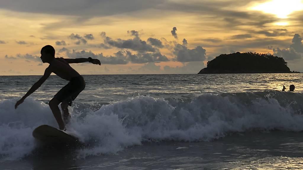 Ein Surfer nimmt vor dem Strand Kata Beach eine Welle bei Sonnenaufgang. Thailand plant, geimpften Ausländern zu erlauben, die südliche Ferieninsel Phuket ohne Quarantäne bei der Ankunft zu besuchen, zur Wiederbelebung der durch die Corona-Pandemie angeschlagene Tourismusindustrie. Foto: Adam Schreck/AP/dpa
