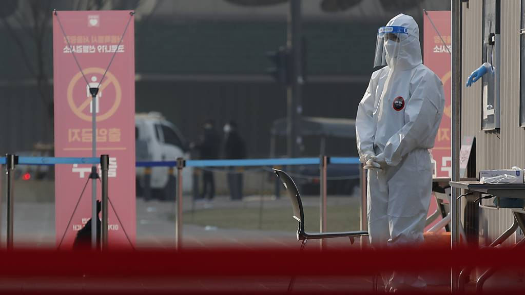 Eine medizinische Mitarbeiterin in Schutzausrüstung steht auf einem Coronavirus-Testgelände. Foto: Lee Jin-Man/AP/dpa