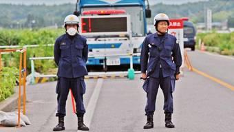 Polizisten am Checkpoint zum Sperrgebiet um Fukushima