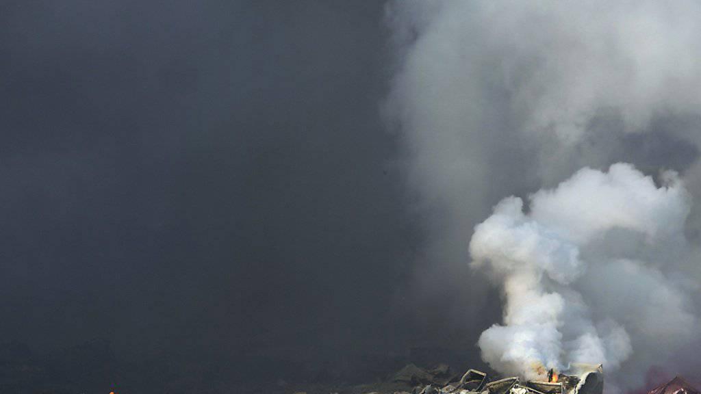 Rauch steigt noch auf, als Feuerwehrleute die Unglücksstelle sichten.