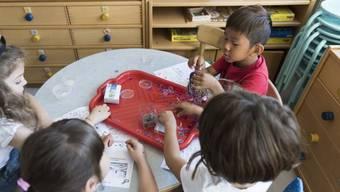 Kindergartenschüler in Suhr experimentieren mit Magneten. Verglichen mit der EU hat die Schweiz noch Nachholbedarf bei der institutionellen frühkindlichen Bildung. (Archiv)