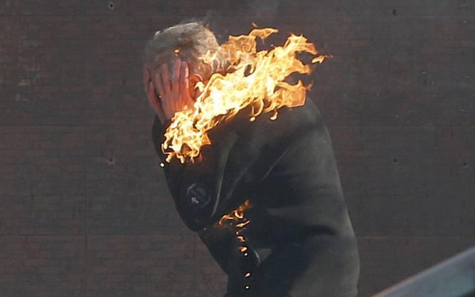 Ein Demonstrant muss sich vor den Flammen retten.