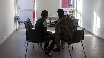 Zwei Flüchtlinge essen in einem Zentrum für junge Asylsuchende. (Symbolbild)