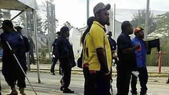 Mit Metallstangen bewaffnete Sicherheitskräfte bei der Räumung des Lagers