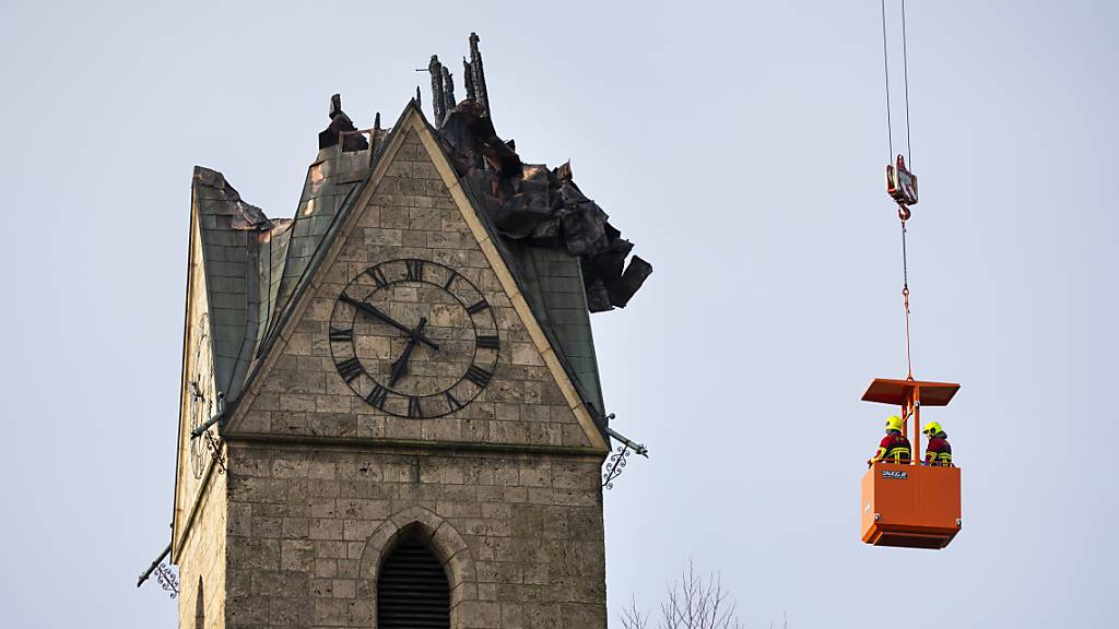 Feuerwehrleute schauen sich die abgebrannte Spitze des Kirchturms in Herzogenbuchsee BE an. Der Sachschaden wird auf mehrere Millionen Franken geschätzt.