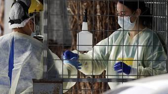 Medizinisches Personal bereitet sich auf die Durchführung eines Coronavirus-Tests bei einem Autoinsassen vor. Die Gesundheitsbehörden in Neuseeland bemühen sich, die Quelle eines neuen Ausbruchs des Coronavirus im ganzen Land ausfindig zu machen. Foto: Mark Baker/AP/dpa