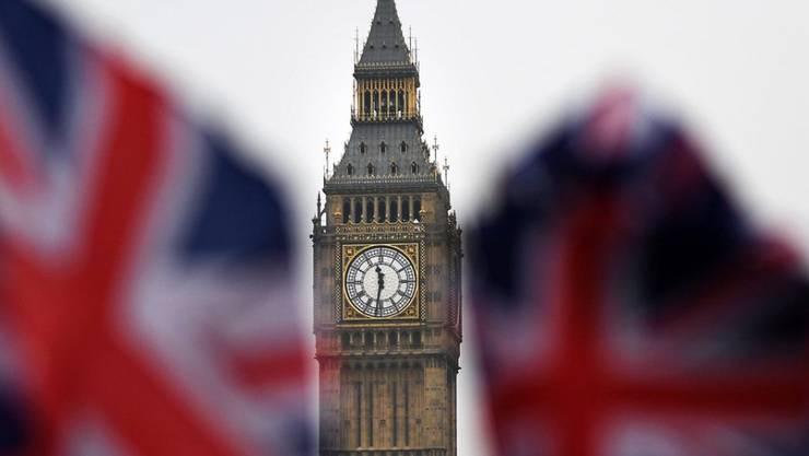 Blick zwischen zwei Union Jacks hindurch auf den Londoner Big Ben. Im Unterhaus begannen am Dienstag die Beratungen über ein Gesetz, das Premierministerin May das Recht einräumen soll, den Abschied nach Artikel 50 der EU-Verträge zu verkünden. (Archiv)