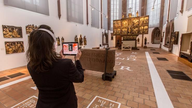 Eine Museumsbesucherin setzt sich mit der virtuellen Welt im Museum für Geschichte auseinander. 500 Jahre alter Stoff wird mit jüngster Technologie in der über 700 Jahre alten Barfüsserkirche veranschaulicht.