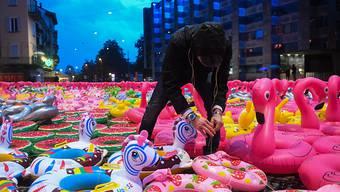 """Künstler Oppy de Bernardo inmitten seines Schwimmring-Kunstwerkes """"Apolide"""" auf der Piazza Grande in Locarno."""
