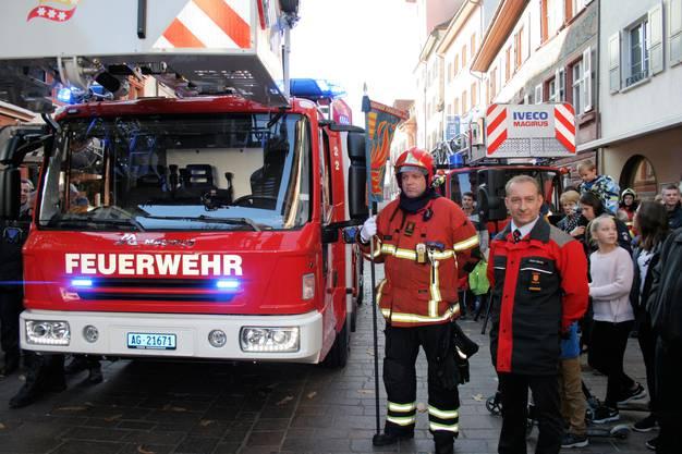Festlicher Empfang Vizekommandanten Marc Leber mit Standarte und Carlo Wernle, Präsident der Beschaffungskommission, vor der neuen Autodrehleiter