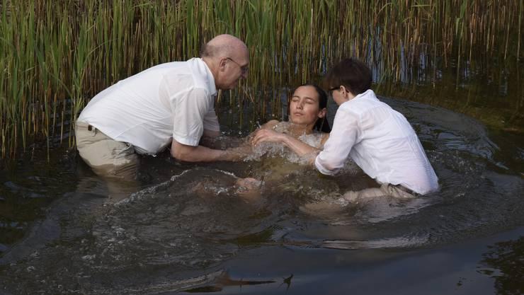 Unterwassertaufe im Weiher: Pfarrer Michel Ummel und Katechetin Isabelle Geiser mit einem Täufling.