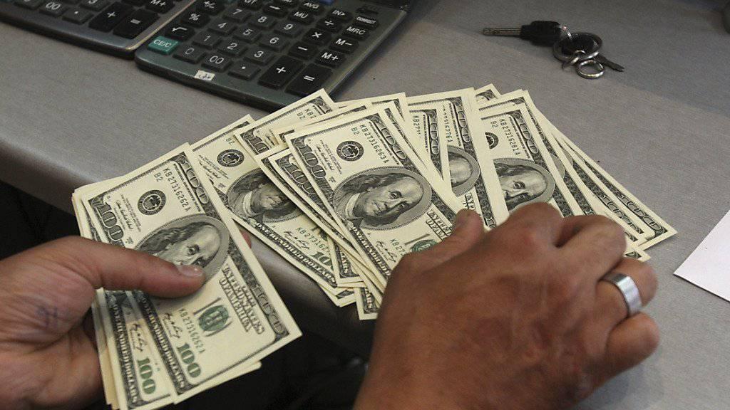 Ein iranischer Geldwechsler zählt Dollarnoten. Der iranische Staat kann nach dem Ende der Sanktionen wieder über 32 Milliarden Dollar verfügen. (Symbolbild)