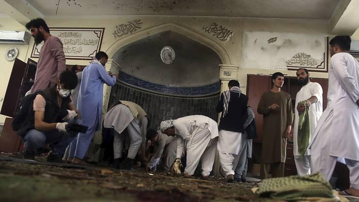 ARCHIV - Männer inspizieren das Innere einer Moschee nach einem Bombenanschlag im Juni. Foto: Rahmat Gul/AP/dpa