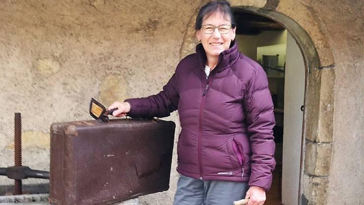Rosmarie Gebhard mit einem Reisekoffer und einem speziellen Milchkessi vor dem Heimatmuseum Schinznach-Dorf. zvg