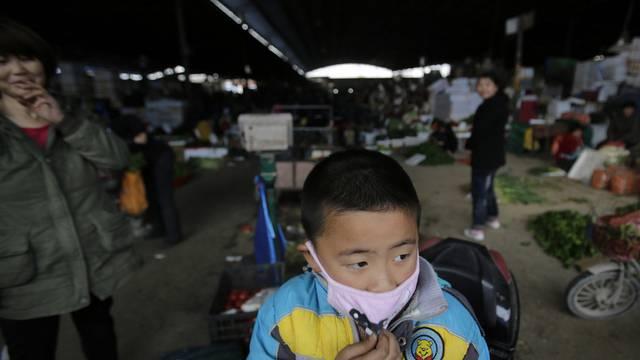 Knabe mit Maske auf einem Geflügelmarkt in Shanghai