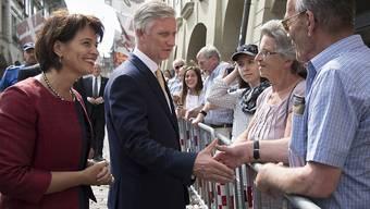 Bundespräsidentin Doris Leuthard (links) begrüsst zusammen mit dem König der Belgier Philippe (Mitte) Schaulustige in der Berner Münstergasse.