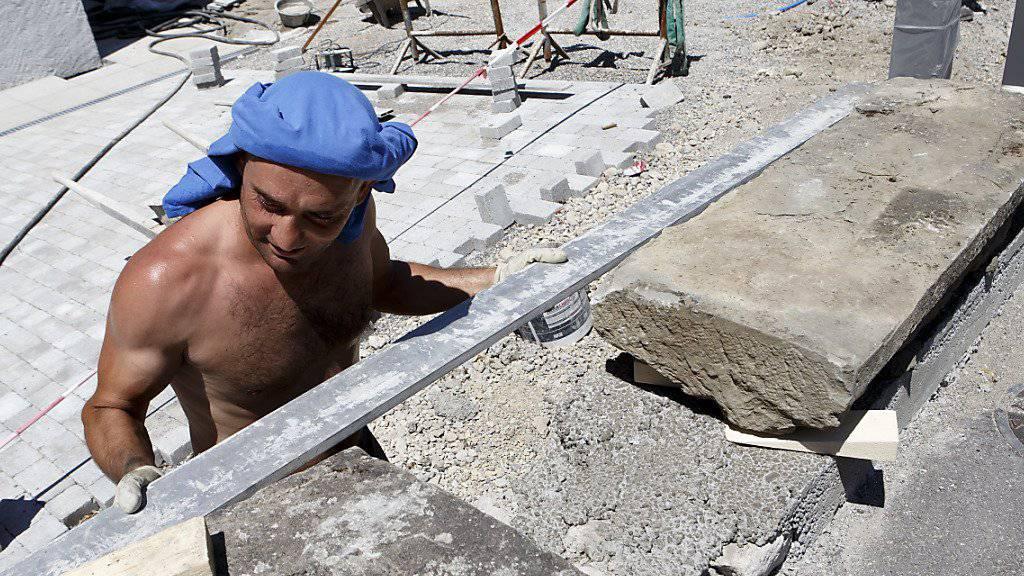Wegen der Hitze ist die Unfallgefahr grösser als sonst: Ein Bauarbeiter arbeitet in Genf an einer Mauer. (Archivbild)