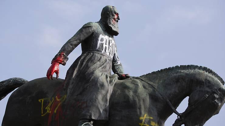 Eine Statue von König Leopold II. von Belgien, die in der Nähe des Königspalastes steht, wurde mit Farben beschmiert und mit dem Schriftzug «Pardon» verziert. Foto: Virginia Mayo/AP/dpa