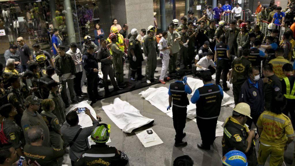 Abgedeckte Leichen liegen vor der Siam Commercial Bank (SCB) in Bangkok: Acht Arbeiter sind im Keller des Hauptsitzes erstickt.