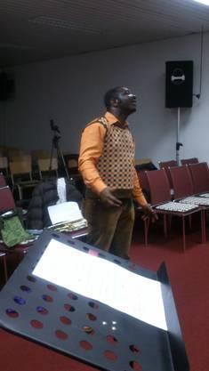 Der engagierte Chorleiter singt gerade die verschiedenen Stimmen vor.