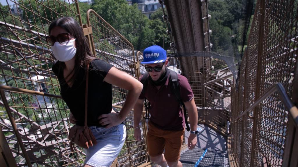 Touristen steigen eine Treppe des Eiffelturms empor. Nach einer über dreimonatigen Zwangspause wegen der Corona-Krise hat der Pariser Eiffelturm am Donnerstag seine Pforten wieder geöffnet. Besucher können zunächst nur über die Treppen den zweiten Stock des Turms erreichen, die Aufzüge sollen erst vom 1. Juli an wieder öffnen.