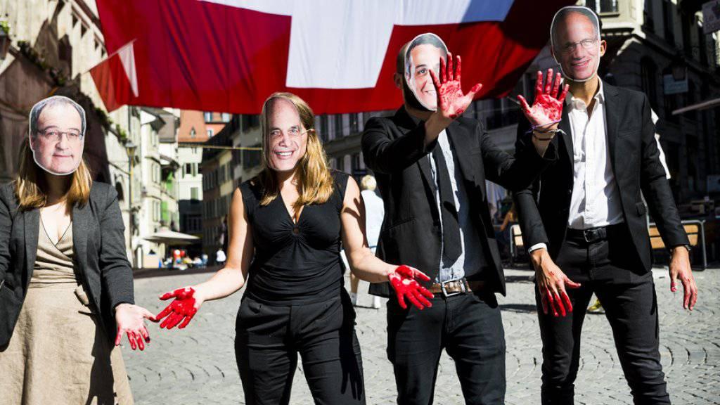 """Nach Ansicht der Gruppe Schweiz ohne Armee (GSoA) ist das Land daran, eine """"blutige rote Linie zu überschreiten"""". Im Bild Aktivisten mit Masken der bürgerlichen Bundesräte Guy Parmelin, Ueli Maurer, Ignazio Cassis, Johann Schneider-Ammann."""