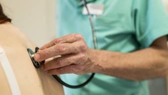 Ein Arzt hört die Lungen einer Patientin ab (Symbolbild)