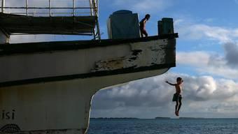 Im Hintergrund die Inseln von Tuvalu. Wird der Meeresspiegel-Anstieg nicht gestoppt sind diese Inseln dem Untergang geweiht.
