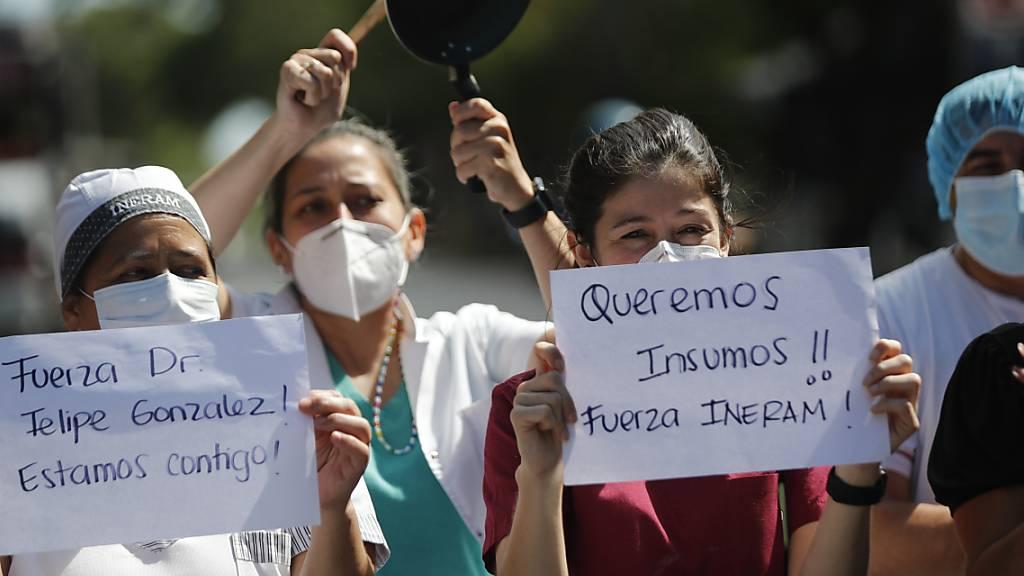 «Wir wollen Arbeitsmaterial», «Halten Sie durch, Dr. Felipe Gonzalez», steht auf den Plakaten von Mitarbeitern eines Krankenhauses, die an einem Protest teilnehmen. Foto: Jorge Saenz/AP/dpa