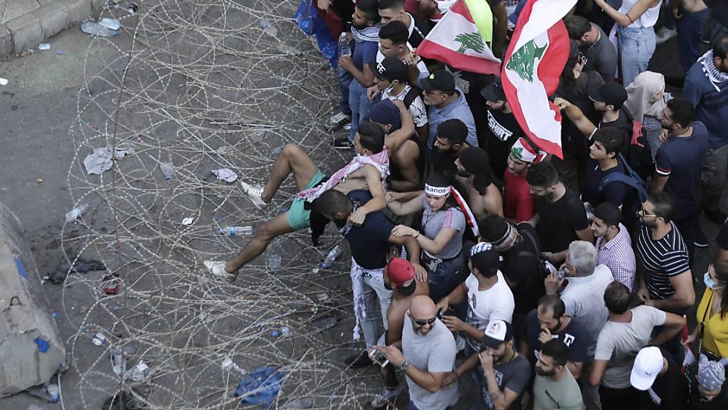 Anti-Regierungs-Demonstranten versuchen in Beirut Stacheldraht zu überwinden und zum Regierungspalast vorzudringen.
