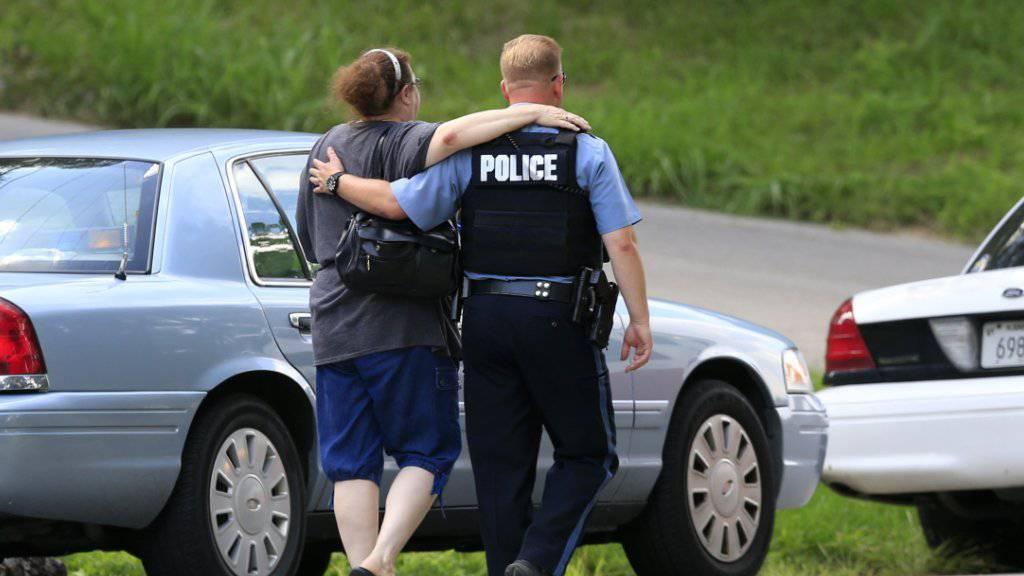 Nach dem Tod eines Polizisten in der US-Stadt Kansas City bringt ein Beamte eine Freundin der Opferfamilie zum Tatort.