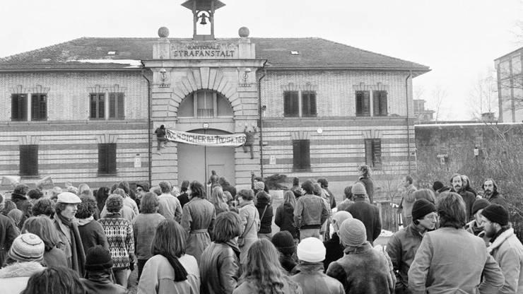 """Sympathisanten des in Regensdorf einsitzenden Walter Stürm führen am 13. Dezember 1980 vor dem Tor der Strafanstalt eine Sympathiekundgebung durch und fordern die Freilassung, beziehungsweise die Aufhebung der Isolationshaft. Ein Transparent mit der Aufschrift: """"Hochsicher ist totsicher» wird an der Gebäudefassade angebracht."""