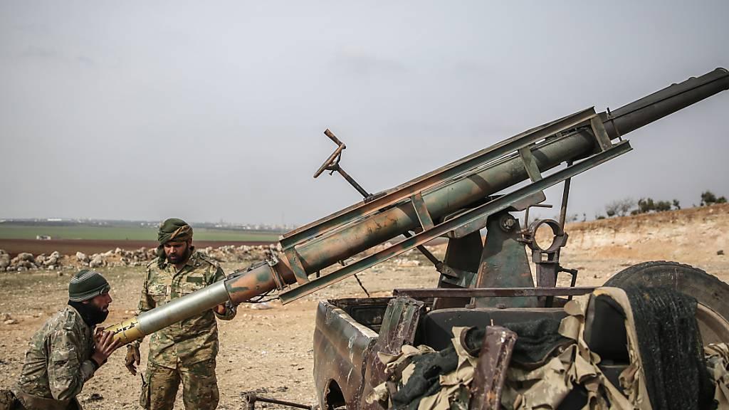 ARCHIV - Von der Türkei unterstützte Soldaten laden einen Raketenwerfer. Die vor fast zehn Jahren in Syrien ausgebrochenen Kämpfe sind 2020 weitgehend abgeklungen. Foto: Anas Alkharboutli/dpa