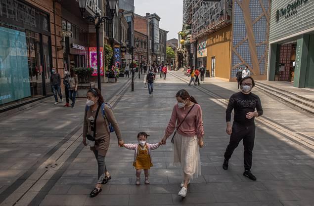 Mit Schutzmasken gehen diese Menschen durch eine Einkaufsstrasse in Wuhan.
