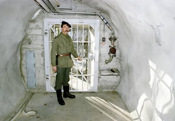 Ein Soldat steht anlässlich einer Presseführung zur Information über die Geheimarmee P-26 beim Eingang der unterirdischen Bunkeranlage bei Gstaad im Berner Oberland, aufgenommen am 7. Dezember 1990. Der Stützpunkt diente der Geheimorganisation als Waffenlager und Ausbildungsanlage.
